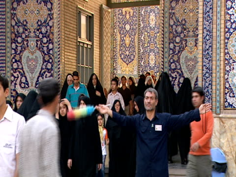 vidéos et rushes de worker directing foot traffic outside of qom shrine / qom, iran - format vignette