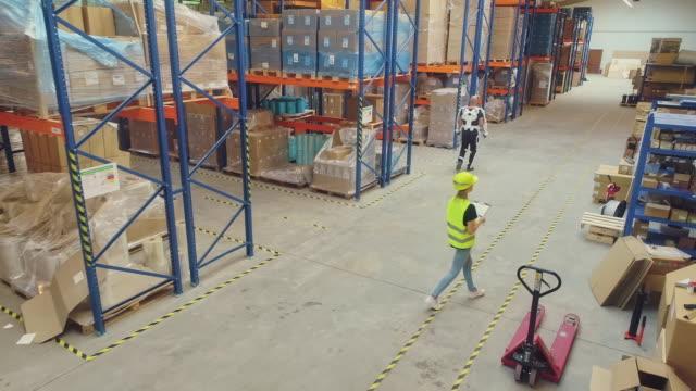 arbeiter, der vorräte im lager verteilt, mit weiblicher managerin. tragen von motorisiertem exoskelett. - hubwagen stock-videos und b-roll-filmmaterial
