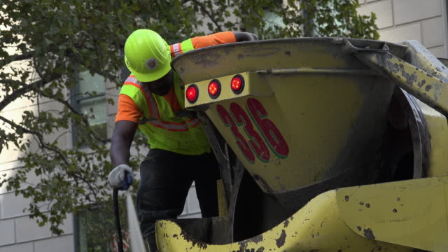 worker doing water cleaning cement truck in new york city - cement mixer stock videos and b-roll footage