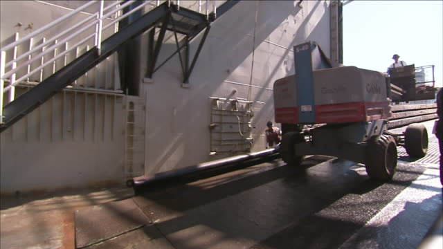 a worker drives a cherry picker by a flight of stairs. - cherry picker stock videos & royalty-free footage