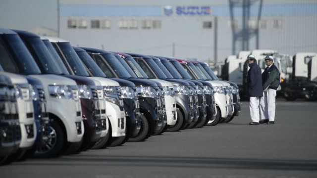A worker drives a Honda Motor Co vehicles bound for shipment at a yard in Yokohama Japan on Monday Dec 15 Workers inspect Honda Motor Co vehicles...