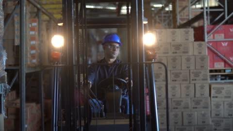 vidéos et rushes de travailleur, conduire un chariot élévateur dans l'entrepôt - machinerie