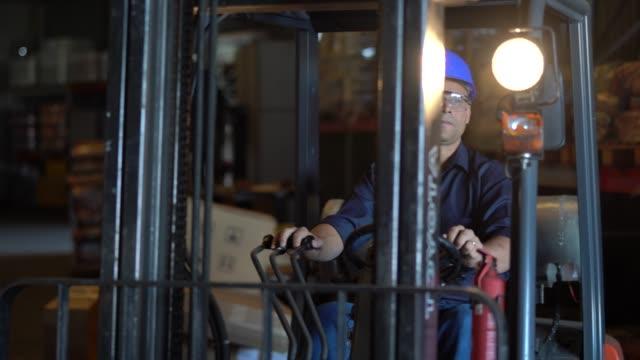vídeos de stock, filmes e b-roll de trabalhador dirigir uma empilhadeira em armazém - estrutura construída