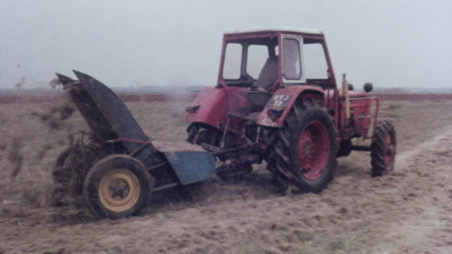 vidéos et rushes de montage worker driving farm machinery over marshland / england, united kingdom - machinerie