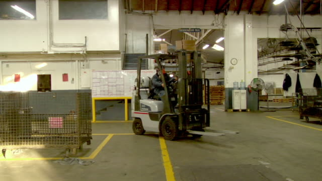 PAN, MS, Worker driving forklift passing by two business people driving electric car in factory, Compton, California, USA