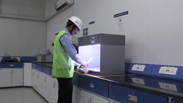 a worker examines the results of a spread test in a laboratory at an akzo nobel india ltd factory in gwalior madhya pradesh india on thursday june 1... - madhya pradesh stock videos and b-roll footage