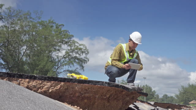 4K DOLLY : worker examing damaged road