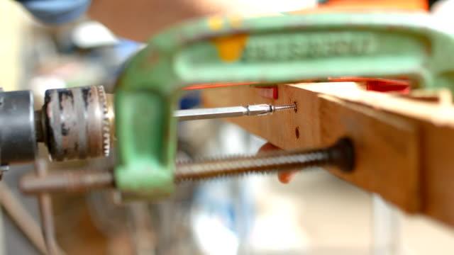 vídeos de stock e filmes b-roll de worker fastening screw on wood beam of table in workshop, dolly shot. - primeiríssimo plano