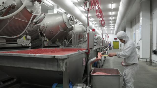 A worker fills a container with a mixture that will be formed into sausages on a production line that manufactures Shuanghui branded sausages at a WH...