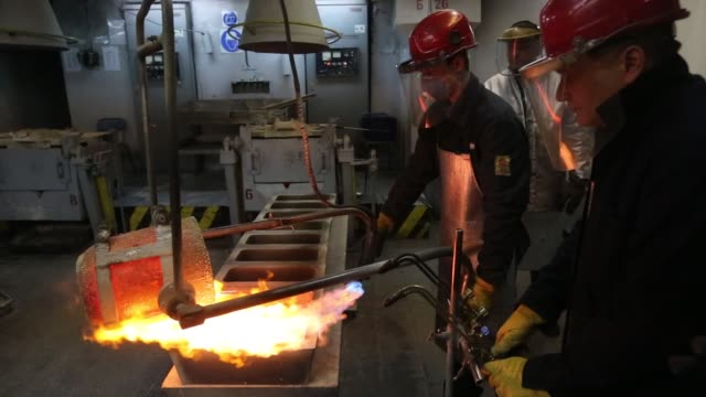 A worker fills a mold with molten silver from a cauldron during the casting of large silver ingots in the foundry at the JSC Krastsvetmet nonferrous...