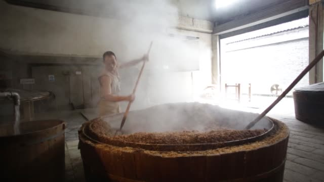 worker fills a steam vat with fermented grain at a baijiu production facility that is part of the shuijingfang museum, operated by sichuan swellfun... - pitchfork stock videos & royalty-free footage