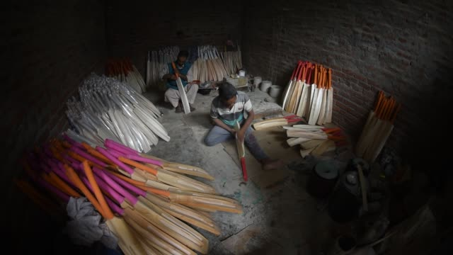a worker finishes cricket bats in a factory on june 08 2019 in halmullah 50 km south of srinagar the summer capital of indian administered kashmir... - クリケットバット点の映像素材/bロール