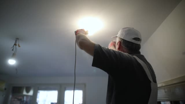 worker finishing works, polishing a ceiling with sandpaper, with light bulb in other hand while standing on ladder - changing lightbulb stock videos & royalty-free footage