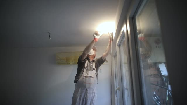 worker finishing works, polishing a ceiling with sandpaper, with light bulb in other hand while standing on ladder - rebuilding stock videos & royalty-free footage