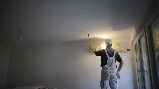 worker finishing works, polishing a ceiling with sandpaper, with light bulb in other hand while standing on ladder - other stock videos & royalty-free footage