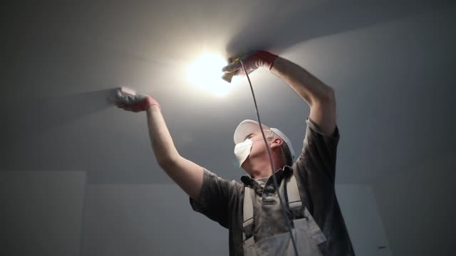 worker finishing works, polishing a ceiling with sandpaper, with light bulb in other hand while standing on ladder - building activity stock videos & royalty-free footage