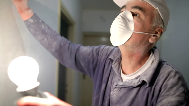 worker finishing works, polishing a ceiling with sandpaper, with light bulb - restoring stock videos & royalty-free footage
