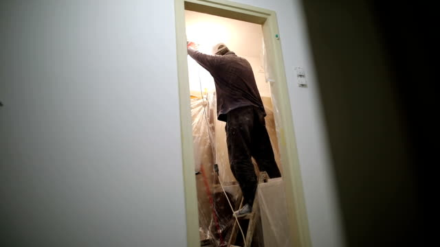 worker finishing works, polishing a ceiling with sandpaper, with light bulb - changing lightbulb stock videos & royalty-free footage
