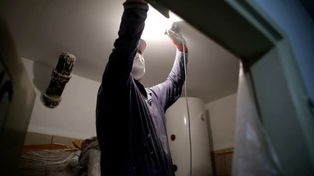 worker finishing works, polishing a ceiling with sandpaper, with light bulb in other hand while standing on ladder - wall building feature stock videos and b-roll footage