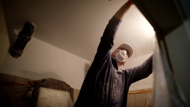 vídeos de stock, filmes e b-roll de trabalhos do revestimento do trabalhador, lustrando um teto com lixa, com a ampola na outra mão ao estar na escada - lixadeira