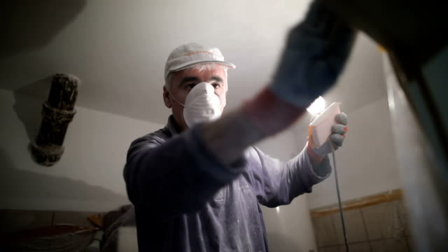 worker finishing works, polishing a ceiling with sandpaper, with light bulb - rebuilding stock videos & royalty-free footage