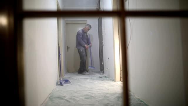 vídeos de stock, filmes e b-roll de trabalhos do revestimento do trabalhador, serragem manual da limpeza do trabalhador com vassoura após a pintura - construindo