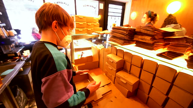worker folds boxes for donuts in the miss mellow battery on fat thursday in warsaw, poland on february 11, 2021. - 四旬節点の映像素材/bロール