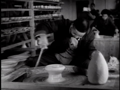 1944 ms worker forming a bowl on a pottery wheel at a porcelain factory, other workers in background / china - bowl stock videos & royalty-free footage