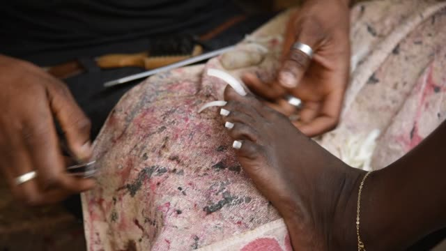 A worker gives a pedicure near Bandim market in Bissau GuineaBissau on Tuesday Feb 13 Photographer Xaume Olleros/Bloomberg