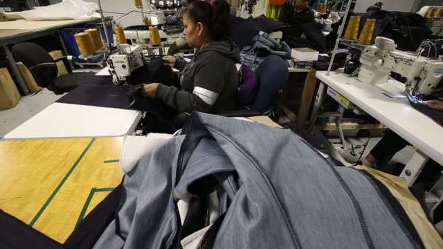 worker grabs denim out of a pile during jeans manufacturing at dearborn denim in chicago illinois november 8 2017 photographer jim young shots... - sy bildbanksvideor och videomaterial från bakom kulisserna