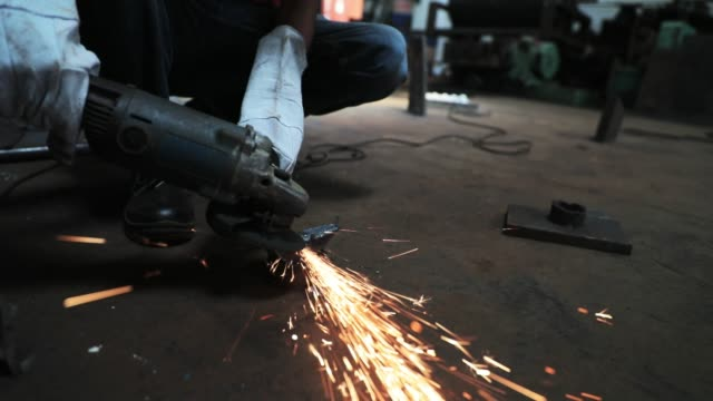 worker grinding a piece of metal at his factory - welding stock videos & royalty-free footage