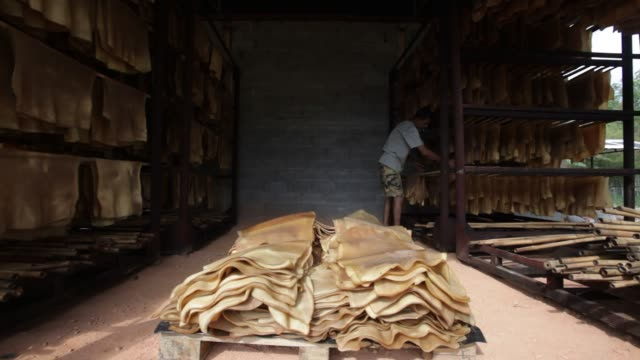 A worker handles rubber sheets at a warehouse in Ban Kokpayom village Songklha province Thailand on Monday May 18 2015 Shots shot of empty rails as...