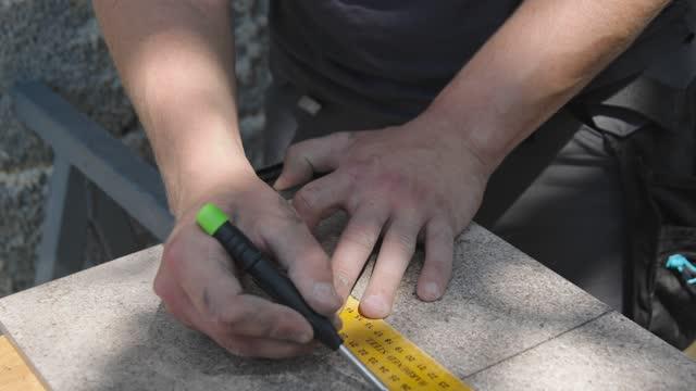 vídeos de stock e filmes b-roll de worker hands marking a line on a tile, using a screwdriver - cerâmica