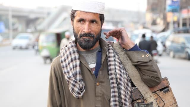 vidéos et rushes de worker holding wooden box with carrying strap. - lahore pakistan