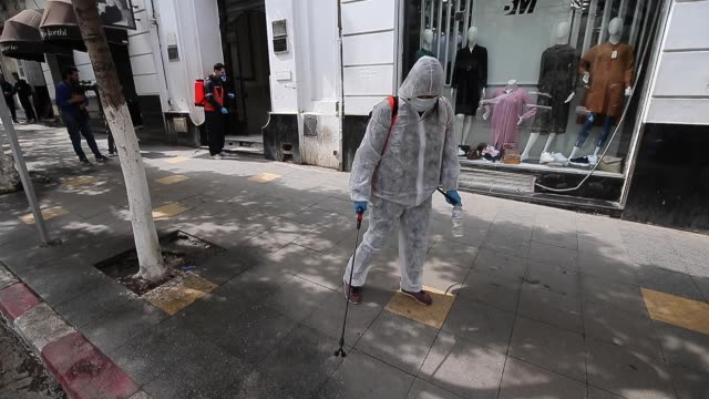 a worker in a protective suit cleanses the streets of algiers after the outbreak of a coronavirus in algiers algeria march 17 2020 - アルジェリア点の映像素材/bロール