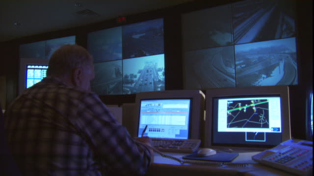 a worker in a traffic center sits in front of an array of computer monitors showing video from traffic cameras. - arlington virginia stock videos & royalty-free footage