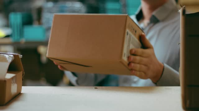 worker in a warehouse puts a box on a shelf - inserting stock videos & royalty-free footage