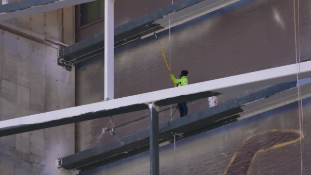 worker in bright yellow jacket paints load bearing beams on a cold winter day. - 桁橋点の映像素材/bロール