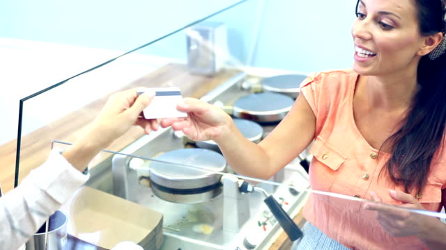 Worker in diner taking credit card payment from customer