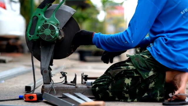 Arbetare i handskar skära ett metallrör