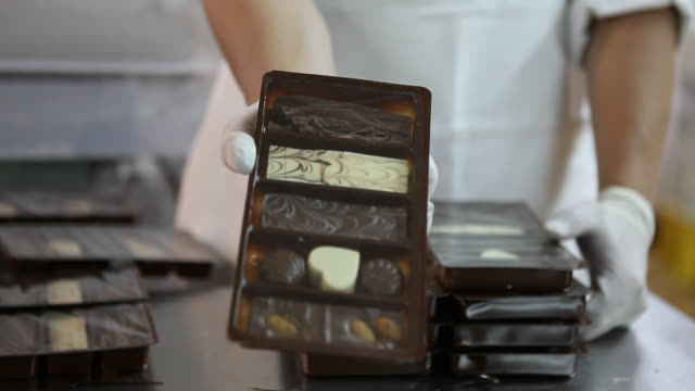 A worker in gloves shows a finished and packed chocolate box in the chocolate factory 'Del Turista' in Bariloche in Patagonia