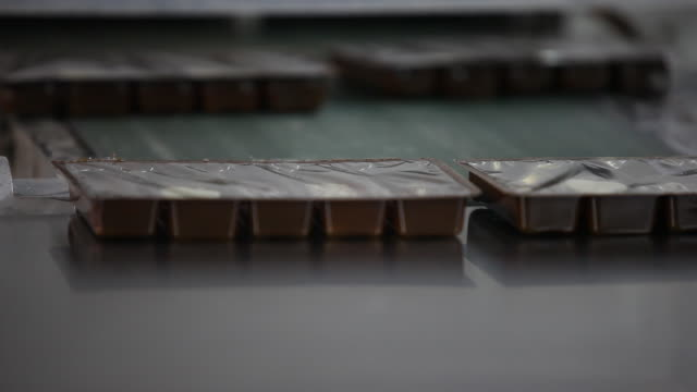 A worker in gloves takes packed chocolate box in the chocolate factory 'Del Turista' in Bariloche in Patagonia away from a conveyor belt