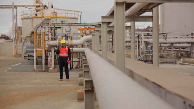 stockvideo's en b-roll-footage met ws worker in hardhat walking around refinery, using walkie-talkie / perth, australia - buiten de vs