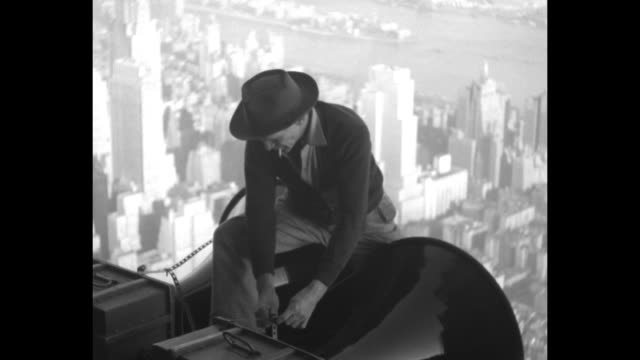 VS worker in hat with cigarette affixes loudspeakers to side of Empire State Building / VS views from behind and underneath speakers to upper levels...