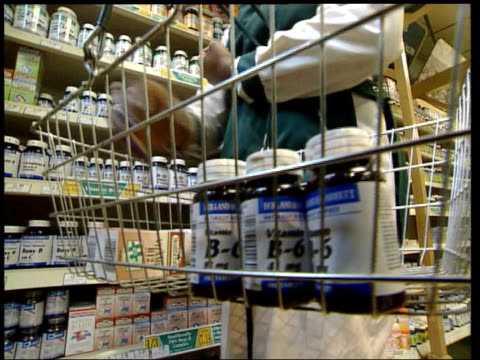 worker in health food shop putting bottle of vitamin b6 capsules on shelf vitamin b6 tablets taken from bottle by woman - health food shop stock videos and b-roll footage