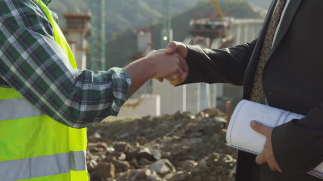 CU worker in high-visibility vest and businessman shaking hands, construction site of freeway bridge in background