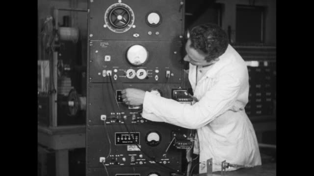 worker in lab coat stands next to a tall collection of electrical equipment with switches lights dials and wires - laborkittel stock-videos und b-roll-filmmaterial