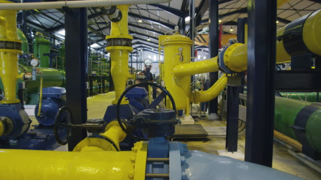 MS worker in maze of tubes in industrial installation (water treatment plant), entering background left and turning big valve; exits frame right, RED R3D 4K