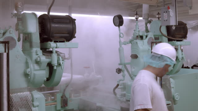 worker in olive processing plant visually inspects lid seal generated by can closing machine / ontario, california, usa  - 缶詰にする点の映像素材/bロール