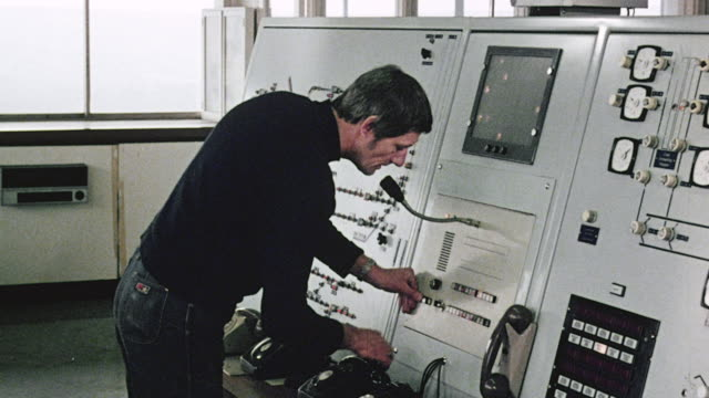 1980 ms worker in power station facing panel of dials, gauges and monitors, nd adjusting controls to signal train / great britain - 1980 stock videos and b-roll footage